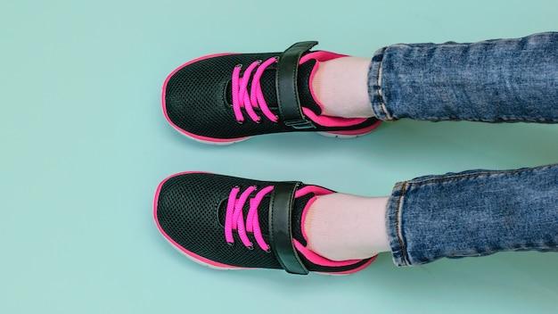 Pernas da garota em jeans rasgados e tênis preto e vermelho
