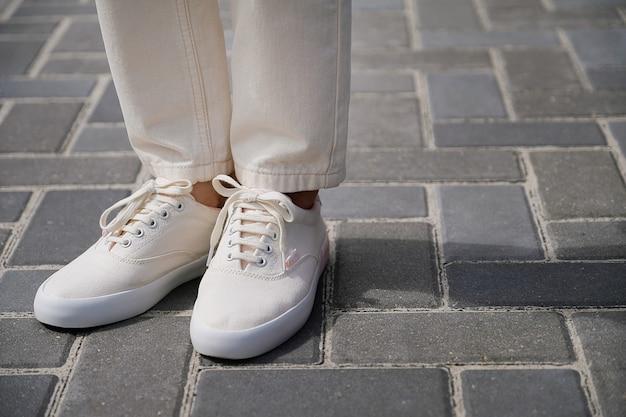 Pernas da garota em novas sapatilhas brancas e jeans