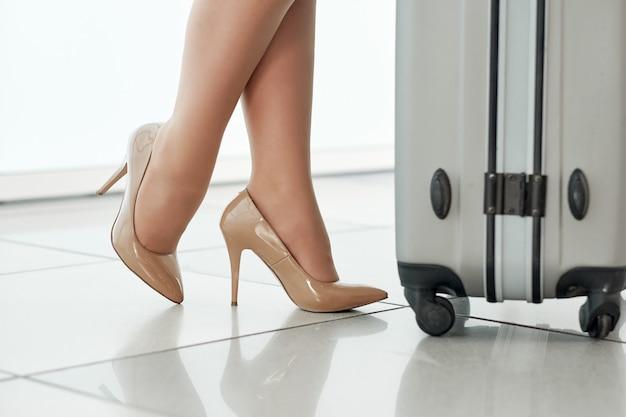 Pernas da jovem empresária com bagagem no aeroporto. viagem de negócios
