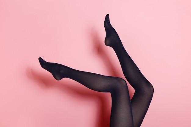 Pernas da jovem mulher caucasiana em meias pretas