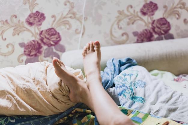 Pernas da menina deitada e descansando na cama, o resto da criança, conforto em casa