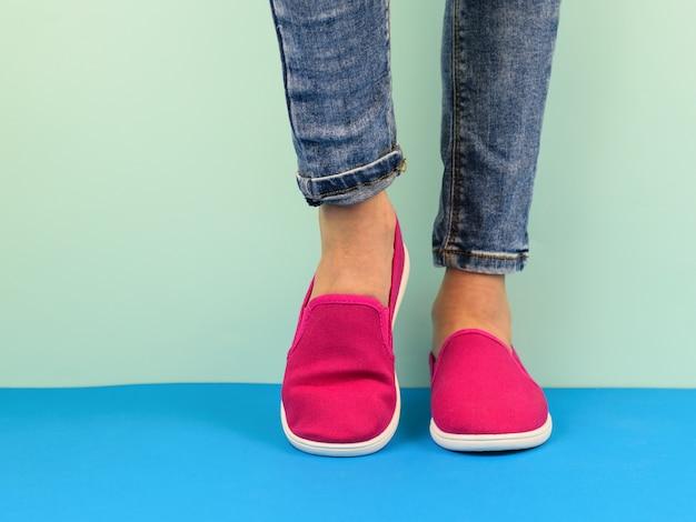 Pernas da menina hippie em jeans no chão azul pela parede azul