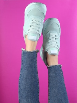 Pernas da mulher em jeans e tênis preto