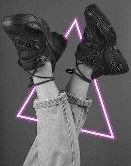 Pernas da mulher em jeans e tênis.