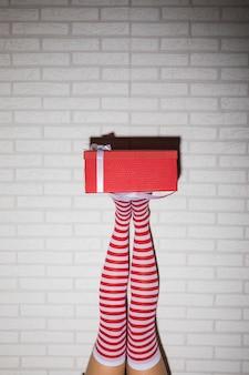 Pernas da mulher em meias com caixa de presente vermelha