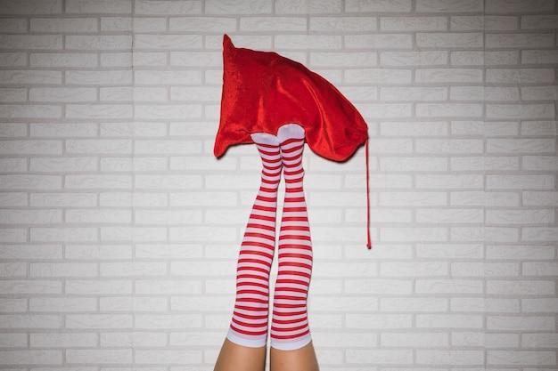 Pernas da mulher em meias com saco vermelho