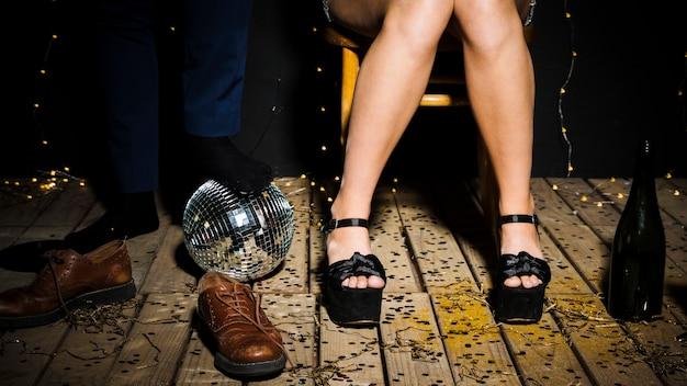 Pernas da mulher em sapatos perto de bola de discoteca e macho