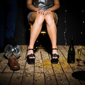 Pernas da mulher em sapatos perto de bola de discoteca, garrafa e macho