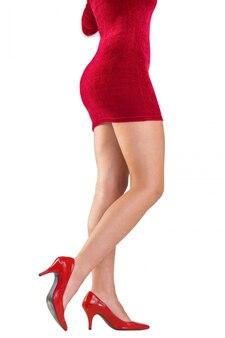 Pernas da mulher festiva de salto alto no fundo branco
