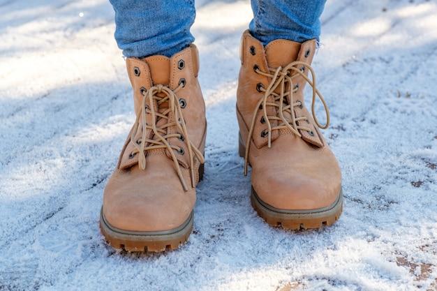 Pernas da mulher nas botas marrons em pé na neve