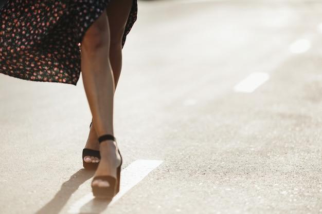 Pernas da mulher no salto alto na estrada no dia ensolarado