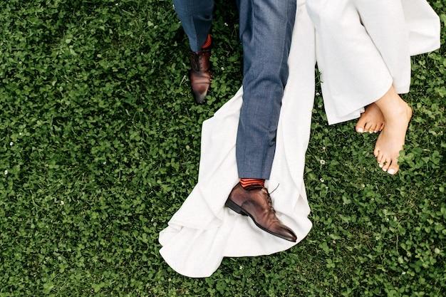 Pernas da noiva e do noivo na grama