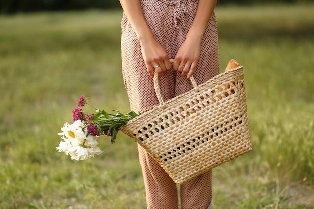 Pernas das mulheres com uma cesta de vime e flores em uma estrada rural