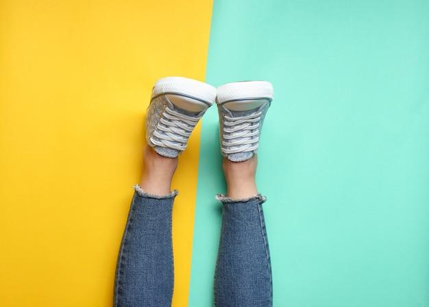 Pernas das mulheres em jeans apertados, rasgados, tênis em amarelo azul pastel. vista do topo