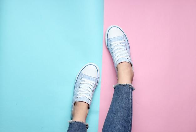 Pernas das mulheres em jeans apertados, rasgados, tênis em rosa azul pastel. vista do topo