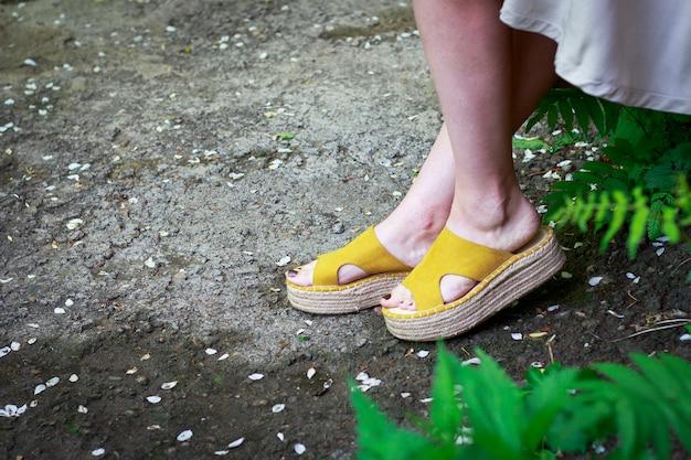 Pernas das mulheres em sandálias de verão elegante com solas de palha,