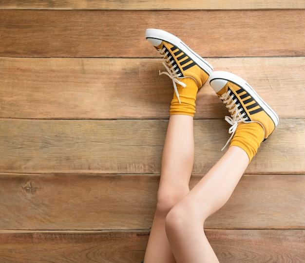 Pernas das mulheres em um tênis de mostarda