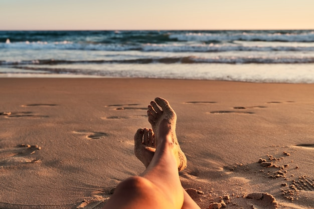 Pernas das mulheres na praia ao pôr do sol
