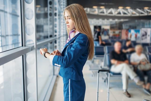 Pernas de aeromoça e mala no saguão do aeroporto