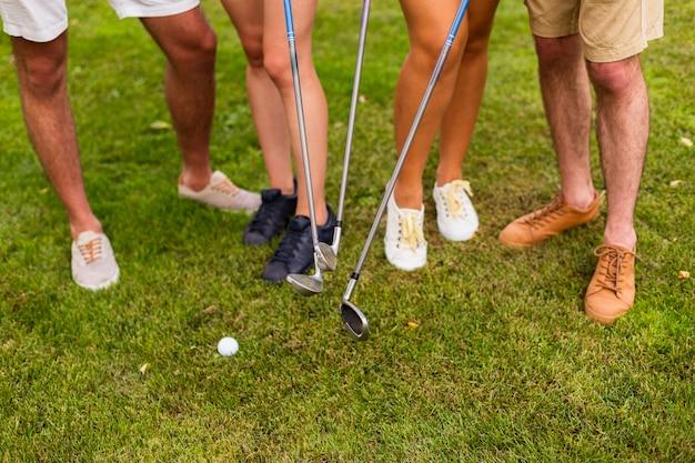 Pernas de alto ângulo de jogadores de golfe com tacos