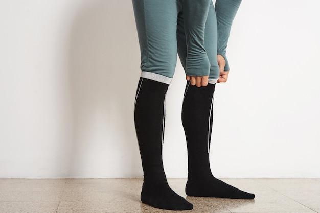 Pernas de atleta masculino em camada de base de inverno e meias térmicas pretas compridas