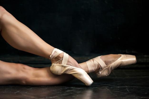 Pernas de bailarina close-up e pointes no chão de madeira preto