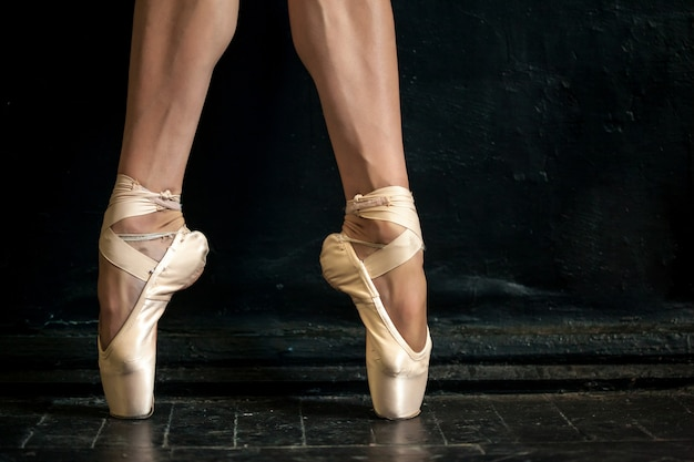 Pernas de bailarina close-up em pointes no chão de madeira preto