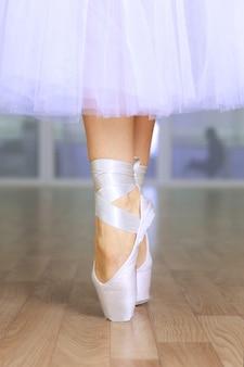 Pernas de bailarina em pointes em salão de dança