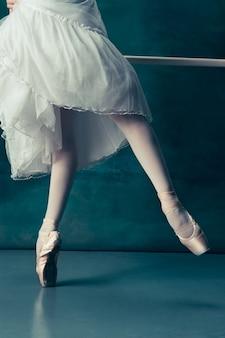 Pernas de bailarinas de close-up em pointes no chão de madeira cinza