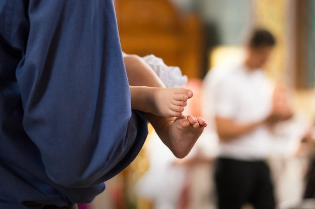 Pernas de bebê nas mãos dos padrinhos na catedral