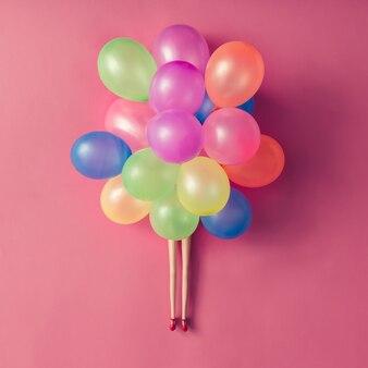 Pernas de boneca com balões coloridos na superfície rosa pastel