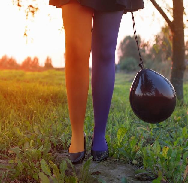 Pernas de bruxa em meia-calça multicolorida com balão preto ao pôr do sol