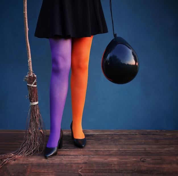 Pernas de bruxa em meia-calça multicolorida com balão preto e vassoura em fundo azul
