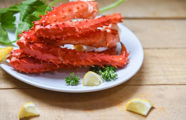Pernas de caranguejo do alasca rei cozido marisco com especiarias limão na chapa branca na mesa de madeira -