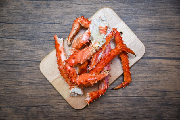 Pernas de caranguejo do alasca rei cozido marisco no fundo de placa de corte de madeira - vermelho caranguejo hokkaido