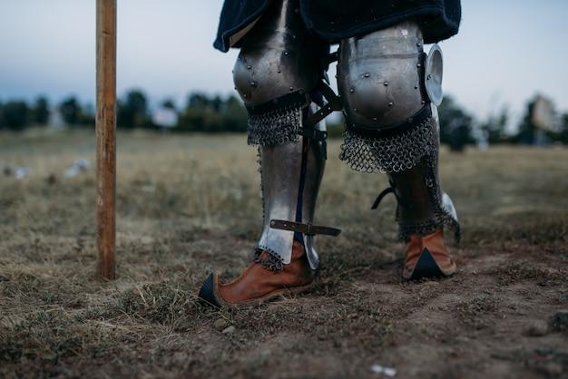 Pernas de cavaleiro medieval em armadura de metal, vista traseira