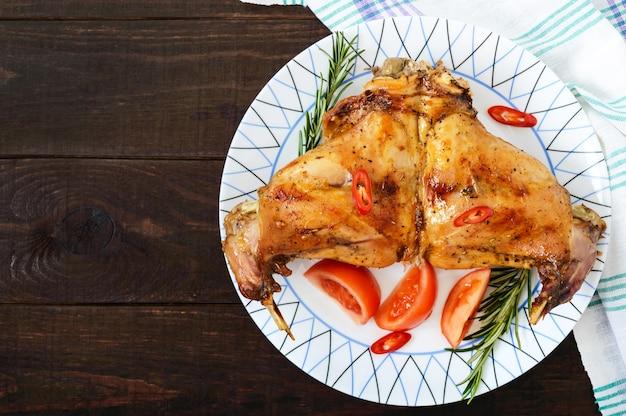 Pernas de coelho assadas em um prato em um fundo escuro de madeira.