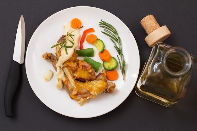 Pernas de coelho assadas em vinho branco com molho bechamel em um prato de cerâmica com faca e garrafa de vinho. carne de coelho dietética cozida no forno. vista do topo.