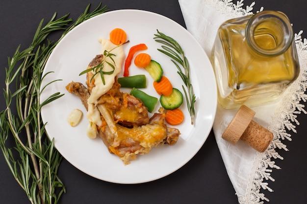 Pernas de coelho assadas em vinho branco com molho bechamel em um prato de cerâmica com legumes e alecrim. carne de coelho dietética cozida no forno. vista do topo.