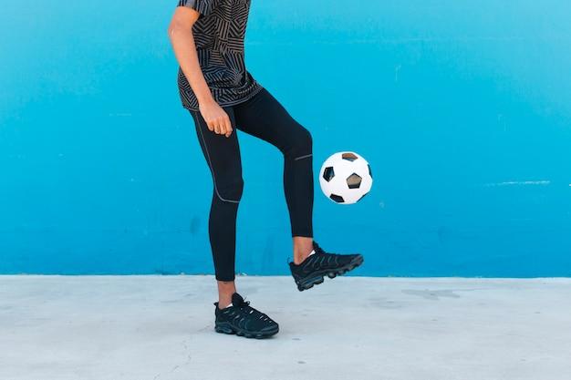 Pernas de colheita do esportista chutando a bola de futebol