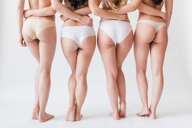 Pernas de colheita do grupo feminino em roupa interior em pé na fila