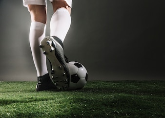 Pernas de colheita e bola no campo