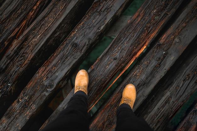 Pernas de colheita na ponte de madeira