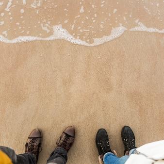 Pernas de colheita perto da água do mar