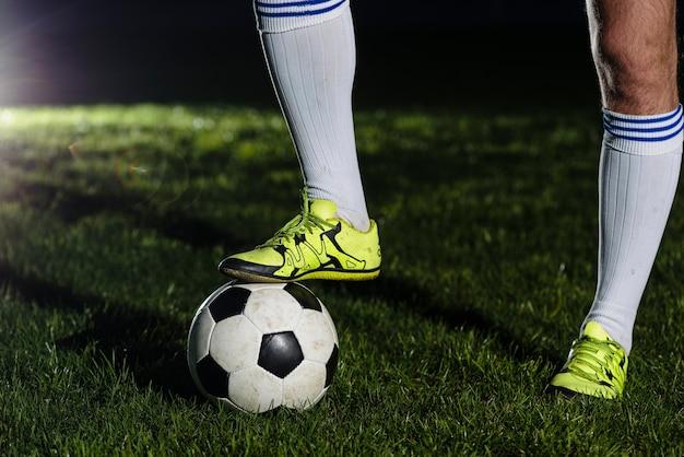 Pernas de colheita pisando na bola de futebol