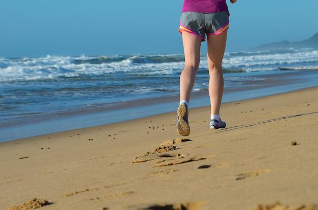 Pernas de corredor de mulher em sapatos na praia, corrida e esporte conceito