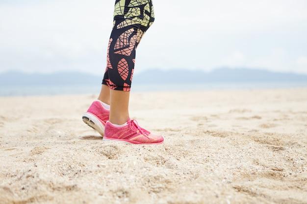 Pernas de corredor feminino e detalhe de calçado desportivo.