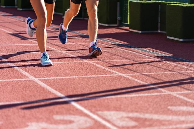 Pernas de corredores correndo em um estádio de borracha na esteira em um dia ensolarado de verão