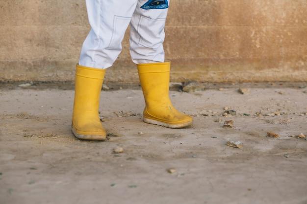 Pernas de criança em botas de borracha