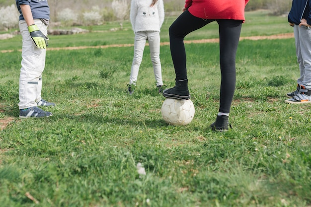 Pernas de crianças jogando futebol